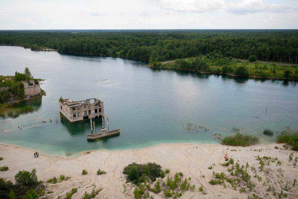 Rummu Quarry, Estonia - July 28, 2015: High angle view of people visiting Rummu quarry in Estonia. For many years the quarry was used as a mining site for Vasalemma marble (a kind of limestone). An adjacent Soviet-era prison supplied most of the workforce. When the quarry and prison closed, so did the pumps that kept the quarry free of rising ground water. Today it is a lake, and a popular place to swim and dive.
