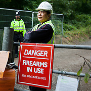 A G4S private security man watches the demonstraters from inside the gates to the site where Cuadrilla wants to run fracking tests.