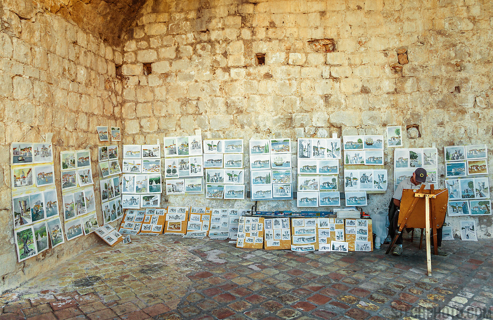 An art vendor and his paintings on the wall surrounding the old city of Dubrovnik, Croatia.