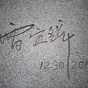 The signature of sculptor Lei Yixin on the side of the main statue of the Martin Luther King Jr Memorial next to the Tidal Basin in Washington DC.