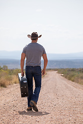 cowboy walking down a dirt road with a guitar