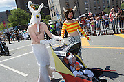 """A family giving homage to the late children's book illustrator Maurice Sendak, in sea creature costumes, and with a sign on their baby buggy """"Where the wild fish are."""""""