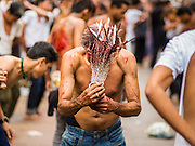 04 NOVEMBER 2014 - YANGON, MYANMAR: A Burmese Shia man hits himself in the head with chains and razors in front of Mogul Mosque (Masjid) on Ashura in Yangon. The flagellation shows solidarity with Hussein and his family. Mogul Mosque is the principal Shia mosque in Yangon. Ashura commemorates the death of Hussein ibn Ali, the grandson of the Prophet Muhammed, in the 7th century. Hussein ibn Ali is considered by Shia Muslims to be the third imam and the rightful successor of Muhammed. He was killed at the Battle of Karbala in 610 CE on the 10th day of Muharram, the first month of the Islamic calendar. According to Myanmar government statistics, only about 4% of the population is Muslim. Many Muslims have fled Myanmar in recent years because of violence directed against Burmese Muslims by Buddhist nationalists.     PHOTO BY JACK KURTZ