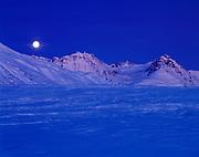 Full moon rising over a wintry Kusawak Range, Northern British Columbia, Canada.