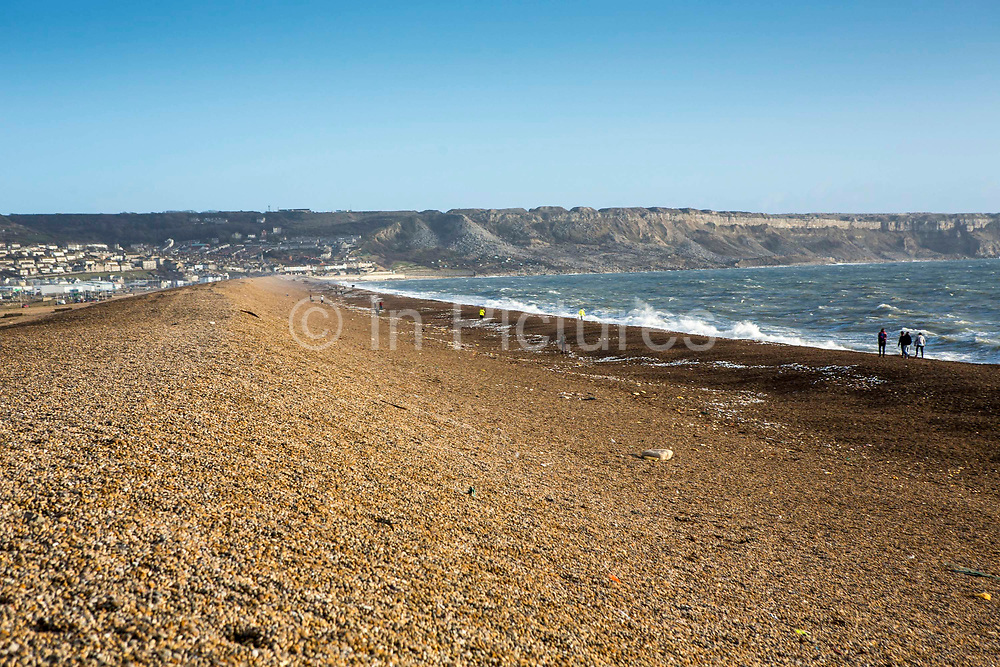 Chesil Beach and the Fleet Lagoon with Portland island in the background with clear blue skies on Jurassic Coast of Dorset, UK.