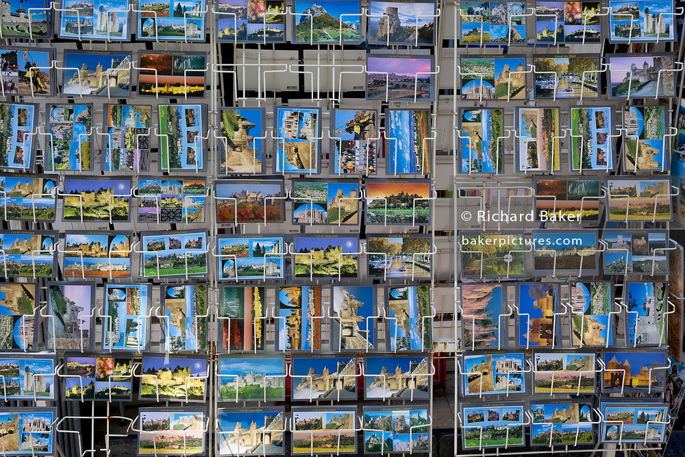 Postcard rack showing local scenes and historical ocations, on 27th May, 2017, in Carcasonne, Languedoc-Rousillon, south of France. Situated on the right bank of the Aude, the City, a medieval village that is still inhabited, has 52 towers and two concentric walls totalling 3 km in length.