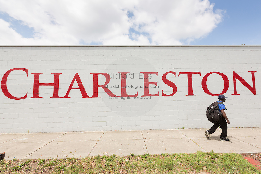 A pedestrian walks past the Charleston Strong wall mural on the eve of the anniversary of the mass shooting June 16, 2016 in Charleston, South Carolina. The wall commemorates the nine people killed at the historic Mother Emanuel African Methodist Episcopal Church on June 17, 2015.