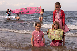 Members of Extinction Rebellion Edinburgh and schoolgirls from Towerbank Primary P3 class joined the UK-wide Make The Wave protest this afternoon on Portobello beach, Edinburgh. The campaign, which starts today - Monday June 7th - is  making its way around the UK coast ahead of the G7 summit in Cornwall, reaching Carbis Bay in Cornwall on June 10th. <br /> <br /> © Jon Davey/ EEm