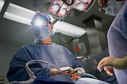 """Mark W. Connolly, M.D., chief of Cardiovascular and Thoracic Surgery at St. Michael's Hospital, sews up the sternum of a patient in an operating room of the hospital in Newark, New Jersey, Wednesday, January 17, 2007. Nisha Vachani, a Physician's Assistant observes.  This particular procedure is known as OPCAB--off-pump coronary artery bypass.  Although it involves opening the patient's chest cavity, it is called a """"minimally invasive"""" procedure since the patient's heart is operated on while still beating, avoiding use of the heart lung machine which is known to add considerable stress to a patient's body.  Special instruments are used to stabilize the heart while the doctor performs surgery.  Many patients are being directed by doctors and consultants to have their heart problems treated with stents--a minimally invasive procedure that does not involve opening the chest cavity--rather than considering the conventional open-heart bypass procedure as a viable option.  It is believed that doctors and consultants pushing stents often do not fully inform their patients of the alternatives that exist, and there is mounting evidence to suggest that thousands of patients die each year who could have lived longer had they undergone bypass surgery."""