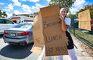 Coral Gables Senior High School cafeteria employee Maria L. Quinones holds up a cardboard sign that promotes free hot grab-and-go meals for all Miami-Dade County School students on Thursday, March 19, 2020.<br /> All Miami-Dade County Public Schools are providing free hot grab-and-go meals for both breakfast and lunch to all students between 9 a.m. and 12:30 p.m. Monday through Friday.