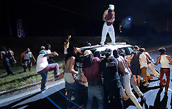 Protestors surround a CMPD vehicle on Old Concord Rd. on Tuesday night, Sept. 20, 2016 in Charlotte, N.C. The protest began on Old Concord Road at Bonnie Lane, where a Charlotte-Mecklenburg police officer fatally shot a man in the parking lot of The Village at College Downs apartment complex Tuesday afternoon. The man who died was identified late Tuesday as Keith Scott, 43, and the officer who fired the fatal shot was CMPD Officer Brentley Vinson. Photo by Jeff Siner/Charlotte Observer/TNS/ABACAPRESS.COM