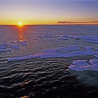 Midnight sun skims the horizon over icebergs floating in the Arctic Ocean, north of Severnaya Zemlya, Russia.