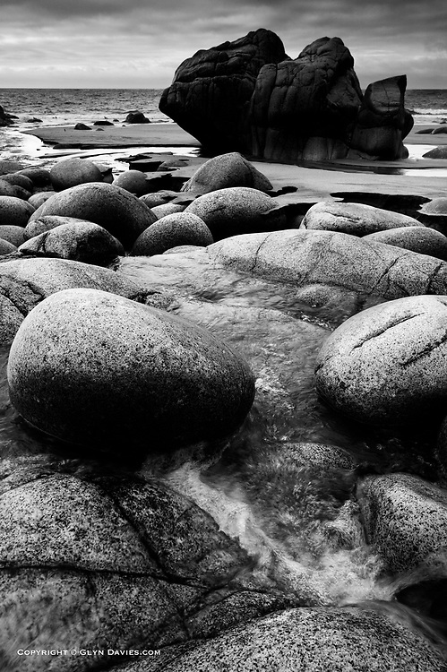 The superb rounded boulders created over thousands of years rolling around in this cove, were strangely and easily covered by shifting levels of grey sand. The gentle river tumbling down from the Cot Valley carved it's own niche, exposing once again the beautiful granite eggs.