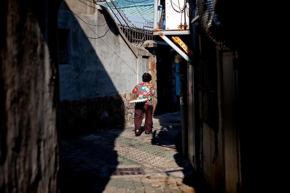 Daegu/South Korea, Republic Korea, KOR, 16.10.2009: Woman walking in an old part of Daegu close to the herbs market for traditional medicine.