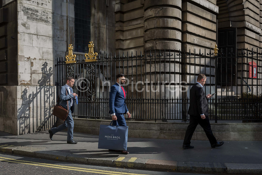 City Businessmen and sunlit railings of St. Mary Woolnoth church on Lombard Street, on 10th May 2017, in the City of London, England. St. Mary Woolnoth is an Anglican church in the City of London, located on the corner of Lombard Street and King William Street near Bank junction. The present building is one of the Queen Anne Churches, designed by Nicholas Hawksmoor. The churchs site has been used for worship for at least 2,000 years; traces of Roman and pagan religious buildings have been discovered. The present building is at least the third church on the site. The Norman church survived until 1445, when it was rebuilt, with a spire added in 1485. It was badly damaged in 1666 in the Great Fire of London but was repaired by Sir Christopher Wren.