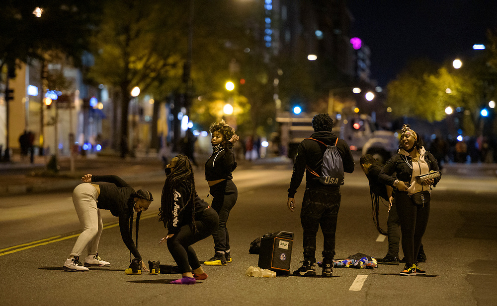 People take advantage of the empty streets to dance while protesters wait for the results of the presidential election nearby at Black Lives Matter Plaza in Washington DC, November 3, 2020.