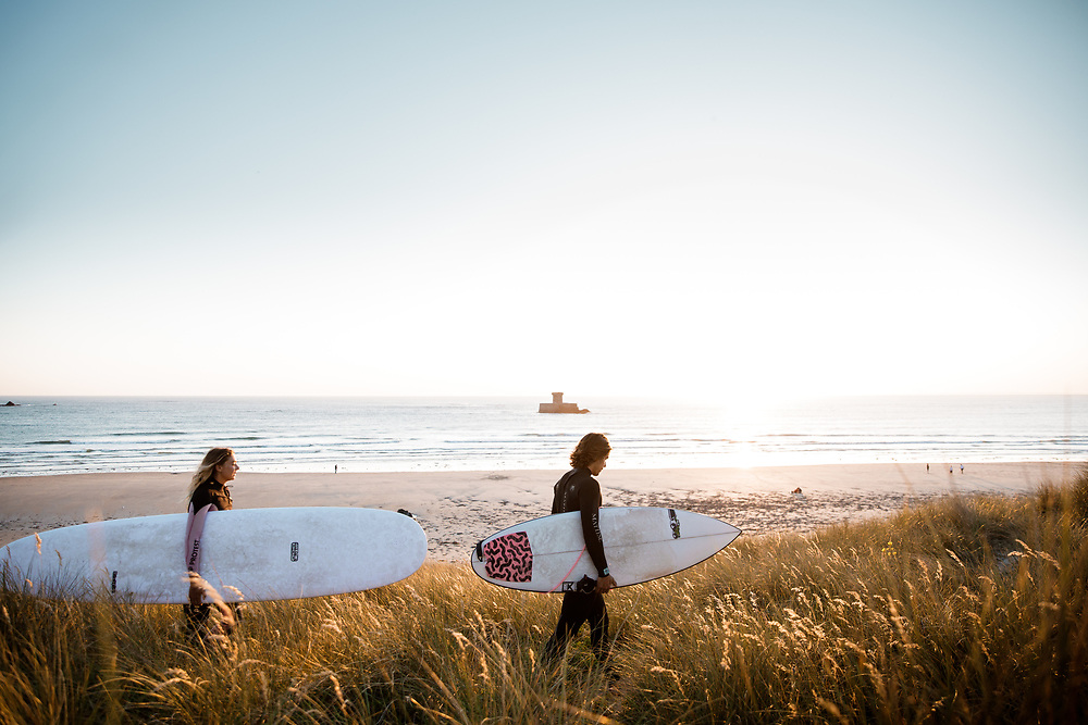Surfers carrying their surfboards, walking through the sand dunes at Le Braye beach in front of La Rocco Tower, St Ouen, Jersey, ready to go surfing in the golden sunlight.