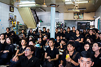 BANGKOK, THAILAND - October 26, 2017: People gather at a local restaurant to watch the late king's funeral procession on TV in Bangkok, Thailand. Hundreds of thousands of people, dressed in black, have gathered in Bangkok over a year after the death of Thailand's popular King Bhumibol Adulyadej.  The five-day royal cremation ceremony is taking place between October 25-29 in Bangkok's historic Grand Palace and the Sanam Luang area.