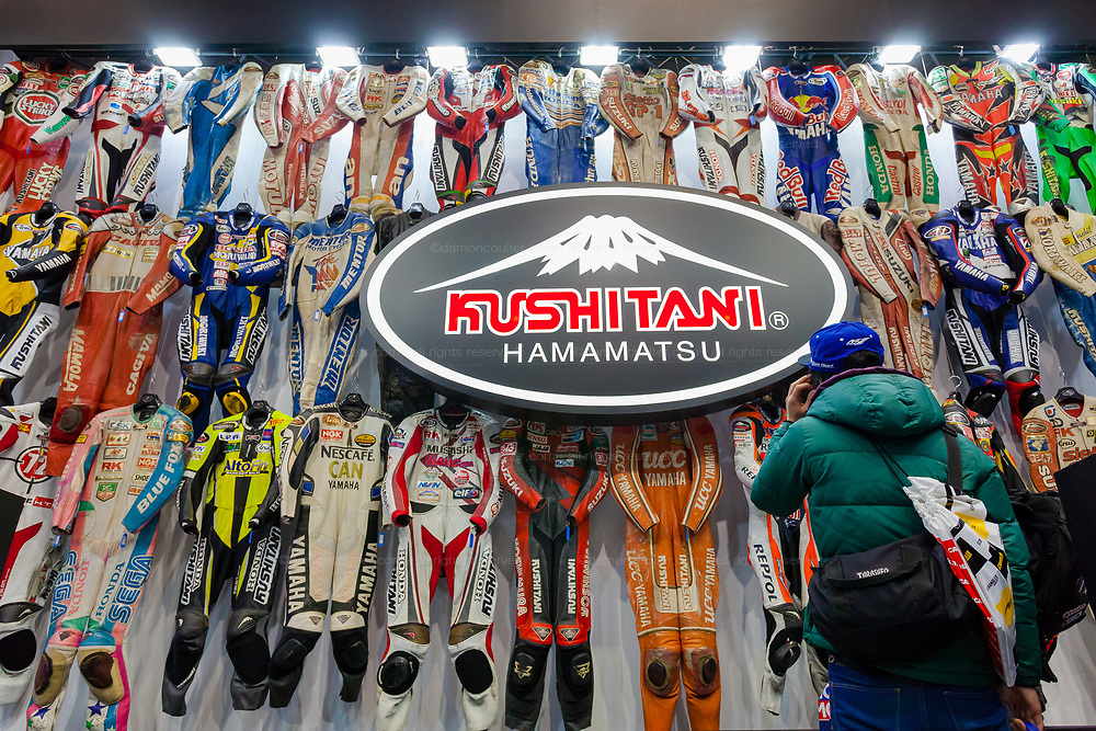 A man looks at a collection of racing leathers worn by famous riders on the Kushitani stand at the 44th annual Tokyo Motorcycle show. Tokyo Big Sight exhibition hall, Odaiba, Tokyo, Japan. Friday March 24th 2017. The show runs from Friday March 24th to Sunday March 26th and showcases technological innovations from all the main motorcycle manufacturers along with companies providing protective helmets pads and  clothing to decoration and even camping gear for bike-touring..