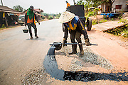 16 MARCH 2013 - ALONG HIGHWAY 13, LAOS: Workers on a road repair crew patch stretches of Highway 13 by putting down gravel and covering it with paving tar. The paving of Highway 13 from Vientiane to near the Chinese border has changed the way of life in rural Laos. Villagers near Luang Prabang used to have to take unreliable boats that took three hours round trip to get from the homes to the tourist center of Luang Prabang, now they take a 40 minute round trip bus ride. North of Luang Prabang, paving the highway has been an opportunity for China to use Laos as a transshipping point. Chinese merchandise now goes through Laos to Thailand where it's put on Thai trains and taken to the deep water port east of Bangkok. The Chinese have also expanded their economic empire into Laos. Chinese hotels and businesses are common in northern Laos and in some cities, like Oudomxay, are now up to 40% percent. As the roads are paved, more people move away from their traditional homes in the mountains of Laos and crowd the side of the road living off tourists' and truck drivers.   PHOTO BY JACK KURTZ