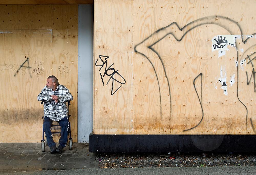 Nederland Rotterdam 20 juli 2008 20080720 Foto: David Rozing .Serie achterstandswijk Afrikaanderwijk, dichtgetimmerd pand aan het Afrikaanderplein. Man schuilt voor de regen. ..Foto David Rozing