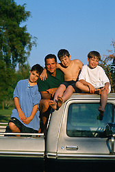 One man and three boys on top of a pick up truck