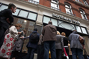 At the height of financial uncertainty, we see from a low pavement angle investors queueing outside the Maddox Street branch of the troubled Northern Rock Bank, off Regent Street, Mayfair, in September 2007. Their hard-earned savings appear to be in jeopardy after the bank announced an emergency loan from the Bank of England. Despite reassurances from officials who insisted that the Bank which has £113bn in assets, was not in danger of going bust, concerned men and women wait in line, some with their faces on view and reading newspapers or more commonly, wishing to remain anonymous and keeping their backs to reporters and cameras. The rush of customers demanding their investments almost spelled the demise of the bank with over £2bn removed from accounts in a few days. Northern Rock struggled since money markets seized up over the summer.