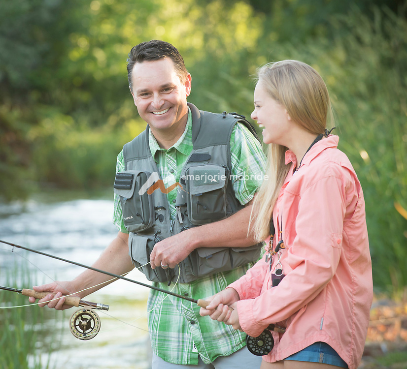 Father and daughter sharing a moment of laughter while fly fishing together at the Billingsley Creek, Idaho. MR
