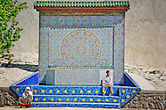 A boy and an old woman at a colourful fountain in Fés, Morocco.