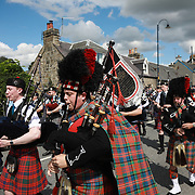 Piper band plays ahead fo the annual Highland Games, 3rd of August 2019, Newtonmore, Scotland, United Kingdom. The band is a mix of various bands from around the highlands. They meet in the centre of Newtonmore and march through the town and out to the playing fields where the games are held. The day is hot and many of the pipers are struggling in the heat. The Highland Games is a traditional annual event where competitors compete as strong men, runners, dancers, pipers and at tug-of-war. The games go back centuries and are happening through-out the summer across Scotland. The games are both an important event locally and a global tourist attraction.