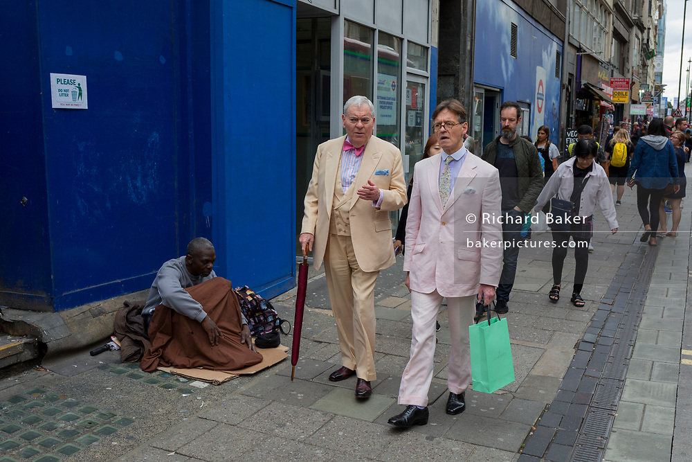 The contrast between two stylishly-dressed gentelmen walking past a homeless man begging on Oxford Street, on 10th August 2017, in London, England.