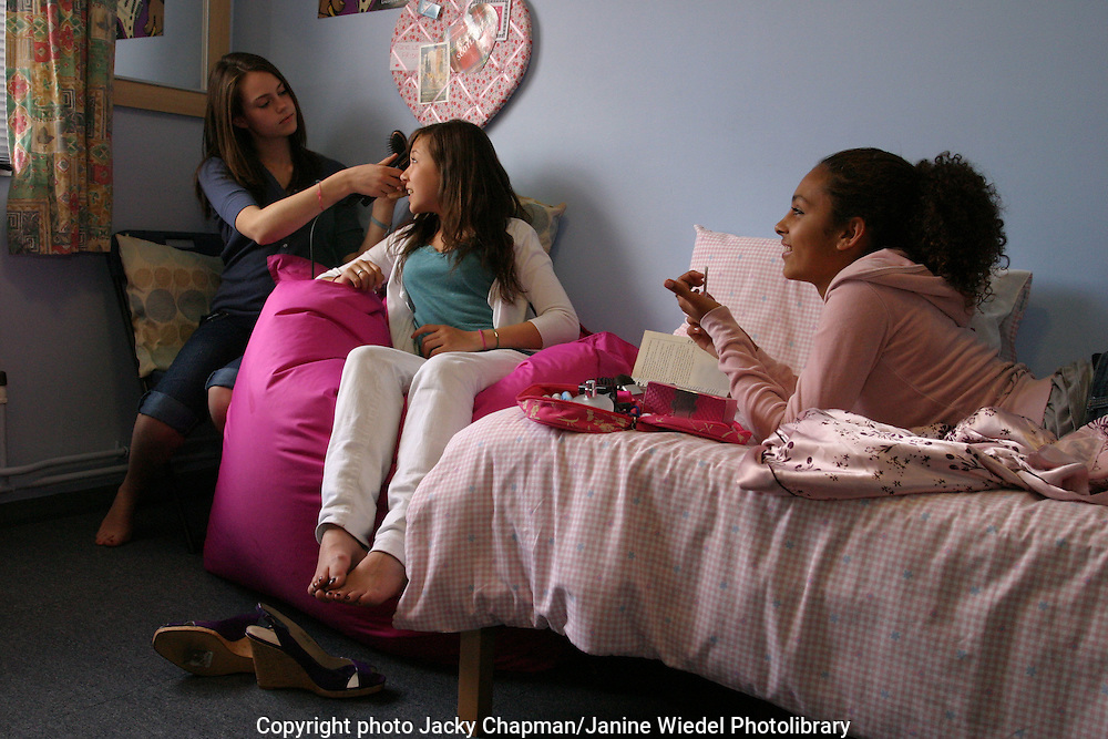 Young Girls at boarding school sitting on the bed chatting bonding and grooming each other.