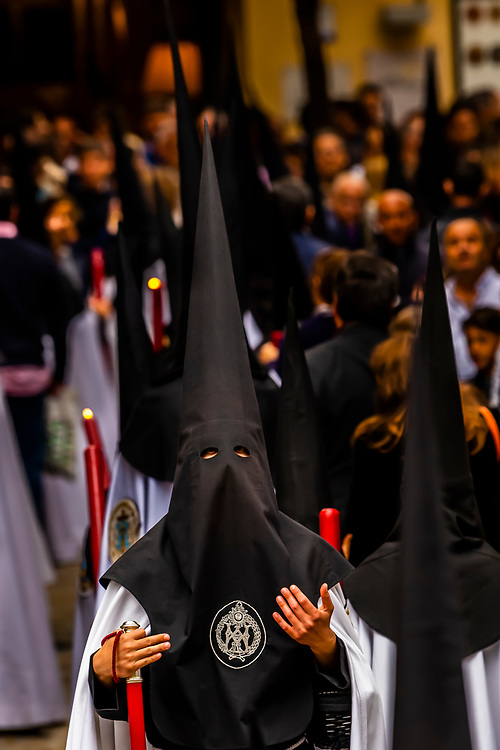 Hooded Penitents (Nazarenos) in the procession of the Brotherhood (Hermandad) La Sed, Holy Week (Semana Santa), Seville, Andalusia, Spain.