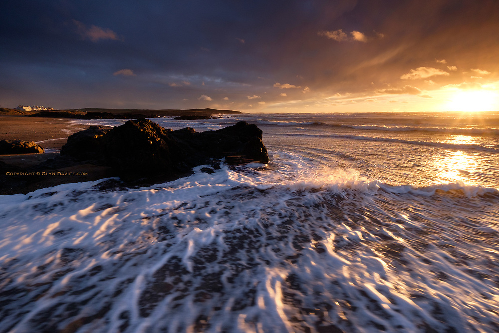 Intense and brilliant low afternoon winter sunlight near Rhosneigr. The strong winds whipped up surf foam, giving the shoreline a creamy appearance