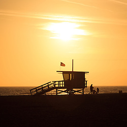 Santa Monica California sunset over the Pacific Ocean with a beach lifeguard tower at Santa Monica State Beach Park in Los Angeles County Southern California.