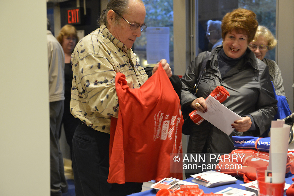 """Oct. 15, 2012 - Hempstead, New York, U.S. - Man attending Simpson and Bowles event at Hofstra puts on red shirt that Fix the Debt Campaign gives free  to anyone who puts in on right there in lobby and wears it to event at Hofstra University's John Cranford Adams Playouse., The campaign's co-founders, Simpson and Bowles, speak in the auditorium about ?America's Debt and Deficit Crisis: Issues and Solutions.? This event with the co-chairmen of the National Commission on Fiscal Responsibility and Reform, and co-leaders of Simpson-Bowles non-partisan U.S. fiscal debt reduction plan, was part of """"Debate 2012 Pride Politics and Policy"""" a series of events leading up to when Hofstra hosts the 2nd Presidential Debate between Obama and M. Romney, the next night, October 16, 2012, in a Town Meeting format."""