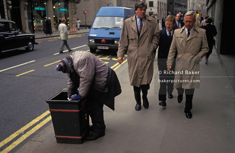As City businessmen walk past during their lunch hour, a homeless man searches through a bin for scraps of discarded food, on 16th June 1994, in the City of London, England.