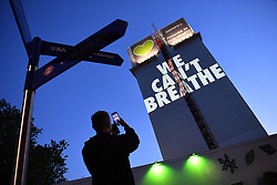 "© Licensed to London News Pictures. 05/07/2020. London, UK.  A man stands in front of a light projection reading 'WE CAN'T BREATHE' cast onto the shell of the of Grenfell Tower in West London on the eve of the second phase of the Grenfell Tower Fire Inquiry. The slogan echoes the words spoken on the night recorded on calls to emergency services and loved ones begging for help that never came. Abbas Dadou, Chairman of Lancaster West Estate Residents Association comprising 800 homes and 2000 residents said ""We stand in solidarity with the families who lost their loved ones in their fight for justice. They are us and we are with them. They are part of our community and their fight for justice is our fight."" El  Alami Hamdan who lost his daughter and his grandchildren in the fire said ""how long must we wait for justice? It has been three years and still nothing. They promise everything and they do nothing""'  <br /> <br /> A press conference will be held this morning ahead of the Inquiry resuming, where a full statement will be released at 10am. ""Family members of those who perished in the fire that took the lives of 72 people on June 14 in 2017 attended the projection of 'We can't breathe' These words echo what we heard on the 999 calls of our loved ones, or the last breath taken by our brothers and sisters, mothers and fathers and our children that night as they begged for help. We have had to listen to these calls as part of the Inquiry reliving their pain and suffering and the failures which cost the lives of our loved ones that night.  We are no longer going to keep silent. We demand justice. We want prosecutions. Our loved ones are not here to speak for themselves and we must speak for them"".  Photo credit: Guilhem Baker/LNP"