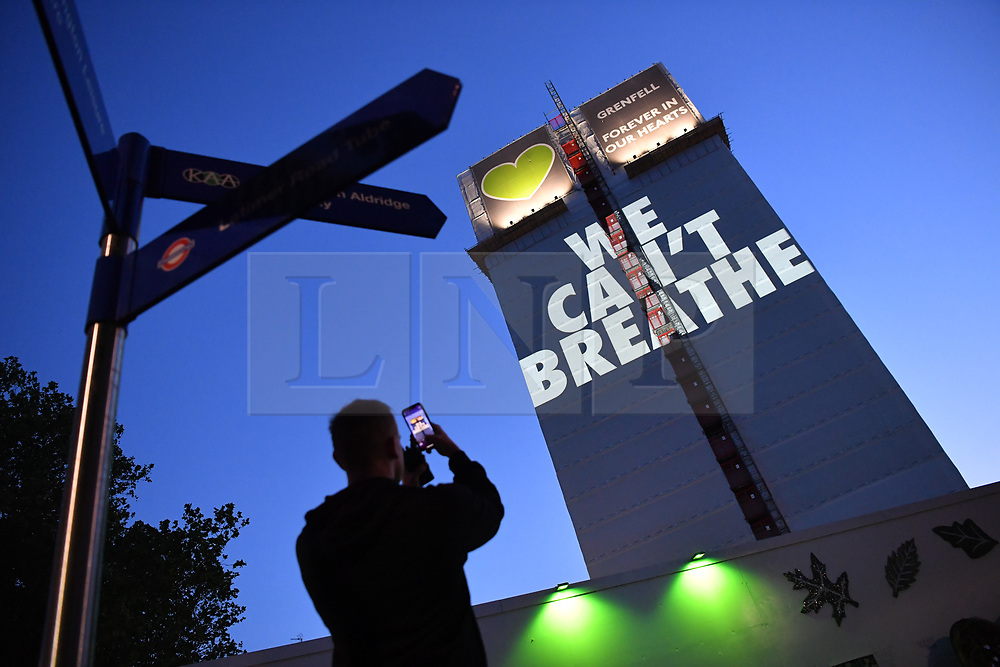 """© Licensed to London News Pictures. 05/07/2020. London, UK.  A man stands in front of a light projection reading'WE CAN'T BREATHE'cast onto the shell of the of Grenfell Tower in West Londonon the eve of the second phase of the Grenfell Tower Fire Inquiry. The slogan echoes the words spoken on the night recorded oncalls to emergency services and loved onesbegging for help that never came.Abbas Dadou, Chairman of Lancaster West Estate Residents Association comprising 800 homes and 2000 residents said """"We stand in solidarity with the families who lost their loved ones in their fight for justice. They are us and we are with them. They are part of our community and their fight for justice is our fight."""" El Alami Hamdan who lost his daughter and his grandchildren in the fire said """"how long must we wait for justice? It has been three years and still nothing. They promise everything and they do nothing""""'<br /> <br /> A press conference will be held this morning ahead of the Inquiry resuming, where a full statement will be released at 10am. """"Family members of those who perished in the fire that took the lives of 72 people on June 14 in 2017 attended the projection of 'We can't breathe' These words echo what we heard on the 999 calls of our loved ones, or the last breath taken by our brothers and sisters, mothers and fathers and our children that night as they begged for help. We have had to listen to these calls as part of the Inquiry reliving their pain and suffering and the failures which cost the lives of our lovedones that night. We are no longer going to keep silent. We demand justice. We want prosecutions. Our loved ones are not here to speak for themselves and we must speak for them"""". Photo credit: Guilhem Baker/LNP"""