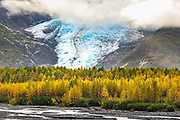 Exit Glacier peaks out of the clouds as it descends to Exit Creek with colorful autumn foliage at the Kenai Fjords National Park near Seward, Alaska.