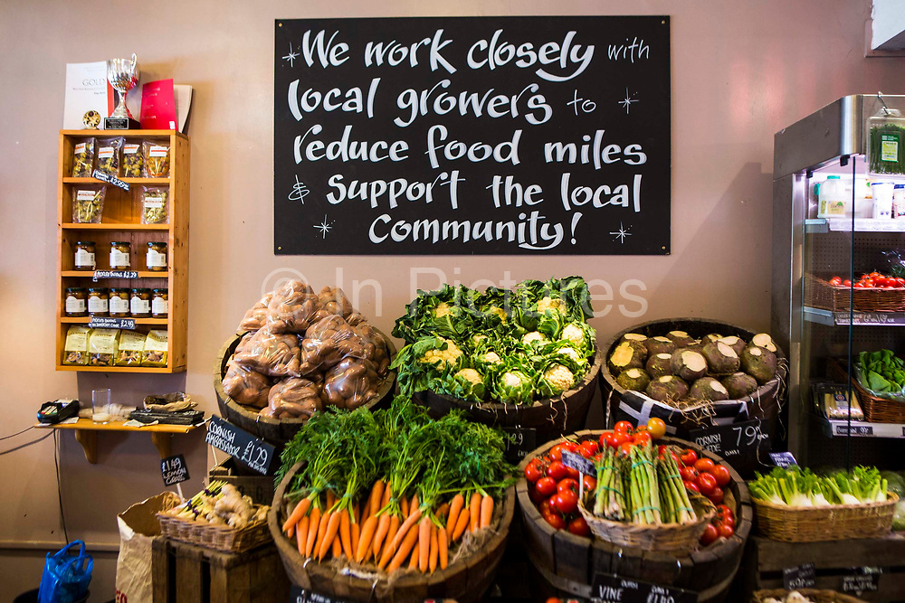 """A variety of locally produced fruit and vegetables on display in a greengrocer and connivence shop in Wadebridge, North Cornwall, United Kingdom. The blackboard informs that the store works """"closely with local growers and suppliers to reduce food miles and support the local community""""."""