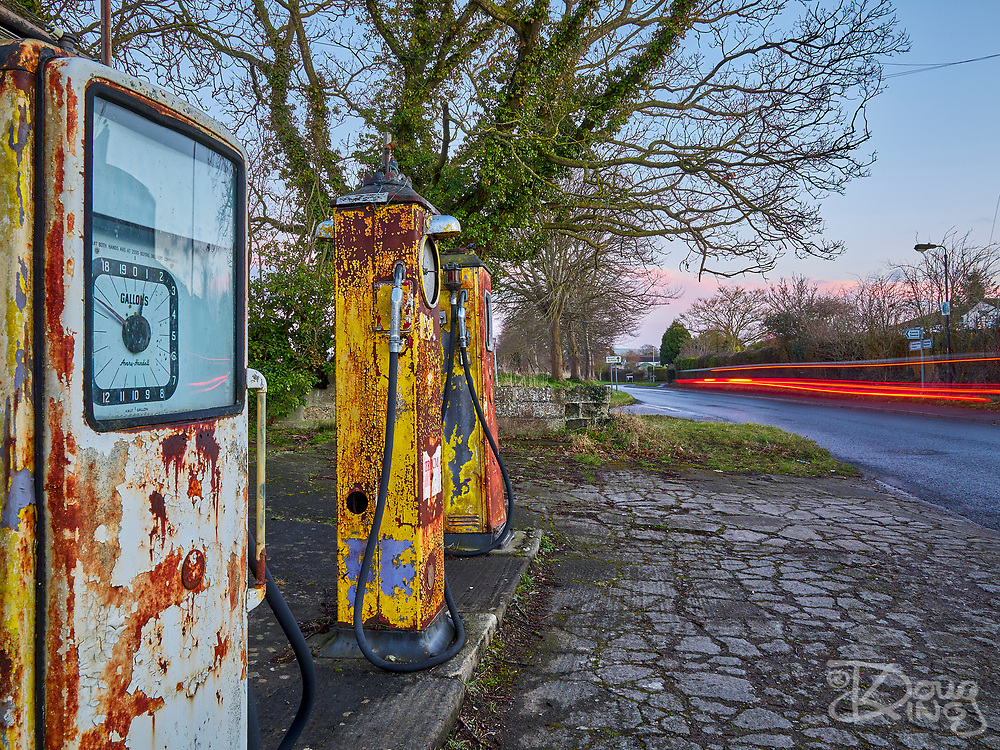 Modern car lights speed past rusty and paint peeling old petrol pumps at a long since closed and abandoned derilict roadside garage and petrol station at Steeple Ashton Wiltshire UK.