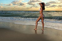 Young african american girl stands in the beach at sunrise.