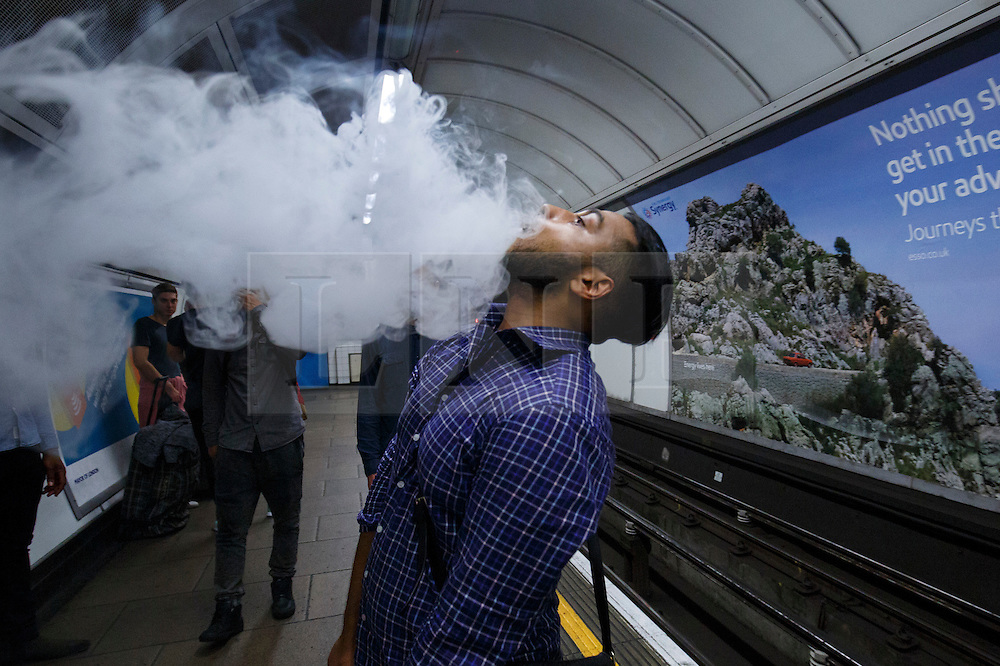 © Licensed to London News Pictures. 20/08/2016. London, UK. A Tube passenger smokes an e-cigarette  whilst waiting for a night tube service of Central line at Oxford Circus station in London for the first time on 20 August 2016. Transport for London started a 24-hour Tube service on Victoria and Central lines as demand has soared over recent years, with passenger numbers on Friday and Saturday nights up by around 70 per cent since 2000. The plan was announced in November 2013 and intended to begin in September 2015, but strikes over pay delayed the start by nearly another year. Photo credit: Tolga Akmen/LNP