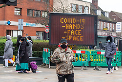 © Licensed to London News Pictures. 01/02/2021. London, UK. Members of the public wearing masks walk past a large Covid-19 information sign in Mitcham Town Centre, South London as door to door testing is to be carried out in London and Surrey after two people tested positive for the South African mutation. Today, two people tested positive in Woking, Surrey for the South African Covid-19 variant by community transmission with no links to South Africa as 800,000 people in England and the South East will be offered urgent Covid-19 tests. Photo credit: Alex Lentati/LNP