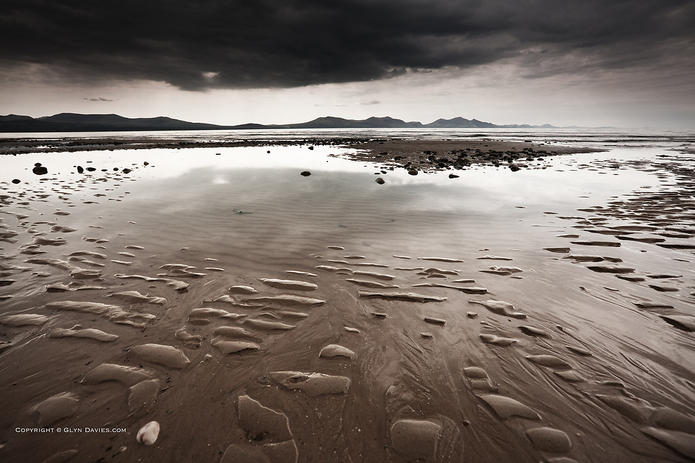Delicate light from wet weather over pools, patterns and textures left at low tide at Llanddwyn Beach, West Anglesey, Irish Sea.