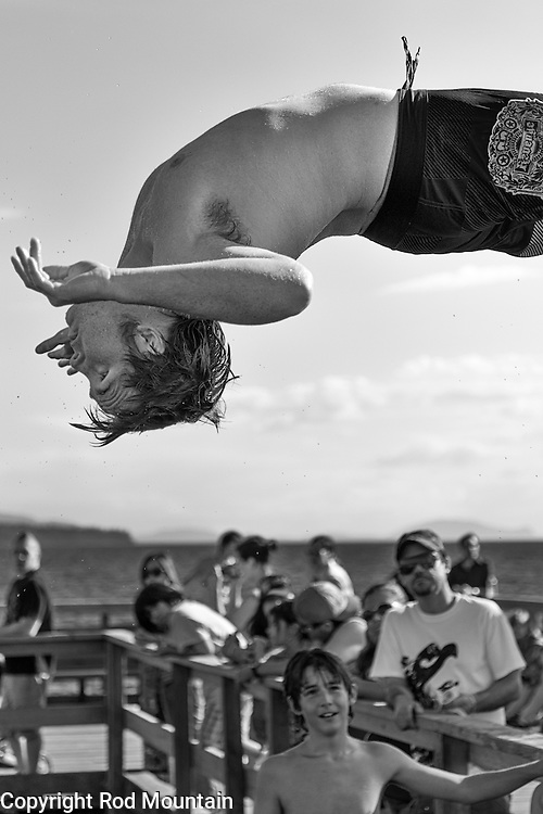 A teenaged boy leaps into a somersault off the pier in White Rock, British Columbia. <br /> <br /> Photo: © Rod Mountain