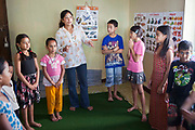 A Nepalese facilitator leads a play session with young street-children in a classroom in the Voice for Children rehabilitation center in Kathmandu, Nepal.  The not-for-profit organisation supports street children and those who are at risk of sexual abuse through educational and vocational training opportunities, health services and psychosocial counseling.  These young children have recently been found by the charity and attend the children's drop-in centre where they play games and activities.