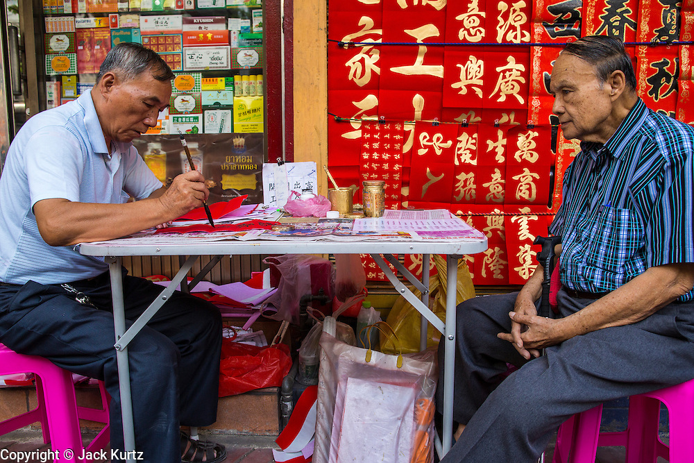 """22 JANUARY 2013 - BANGKOK, THAILAND:  A customer (right) watches calligrapher work on Chinese New Year at his table on Charoen Krung Road in Bangkok's Chinatown district. Chinese New Year is not an official public holiday in Thailand, but it is one the biggest celebrations in the Bangkok, which has a large Chinese population. Chinese New Year is February 10 this year. It will be the """"Year of the Snake.""""     PHOTO BY JACK KURTZ"""