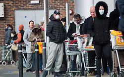 © Licensed to London News Pictures. 29/03/2020. London, UK. A long line of shoppers queue to enter Sainsbury's at Ladbroke Grove in west London during a lockdown to slow the spread of COVID-19. Members of the public have been told they can only leave their homes to exercise briefly once a day, and to go to shops for essentials when absolutely necessary, in an attempt to fight the spread of COVID-19. Photo credit: Ben Cawthra/LNP